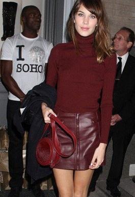 她以酒红色高领衣搭配性感的皮革拉链短裙